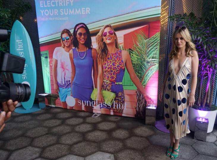 Georgia May Jagger poses in front of her Electrify Your Summer Campaign with Sunglass Hut